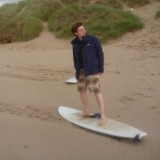 Me riding a surfboard in the wind on some sand
