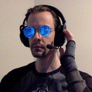 a portrait of Midas wearing large headphones and round sunglasses. Reflected in the blue mirror sunglasses is a computer screen displaying program code.